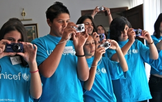 Children try out new digital cameras in the south-eastern town of Pirot. They are among 19 children and adolescents, ages 11–18, participating in the UNICEF child photography workshop in the town. Fourteen of the participants are girls. The children are wearing T-shirts with the UNICEF logo.  In May 2013 in Serbia, UNICEF facilitated a five-day photography workshop for 19 children aged 11 to 18 years from Roma and Serbian communities in the south-eastern municipality of Pirot, near the Bulgarian border. Guided by UNICEF photographer and workshop trainer Giacomo Pirozzi, the participants, 14 of whom were girls, learned about image framing and composition in addition to basic camera functions. The workshop gave the children an opportunity to photograph their world and share their views and experiences with others. The project is part of a series of UNICEF 'EYE SEE' child photography workshops in partnership with Sony Corporation in different countries around the world. The 'EYE SEE' workshop in Serbia was the first held in Europe. The children's photographs will be exhibited first in Belgrade, the capital, then afterwards in seven municipalities in southern and eastern Serbia – including Pirot – where UNICEF, local authorities and civil society are supporting model community centres to provide education and innovative services in Roma communities.